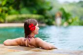 picture of infinity pool  - Beautiful woman relaxing in infinity swimming pool - JPG