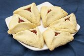 image of apricot  - apricot hamantaschen cookies  on a plate against blue tablecloth  - JPG