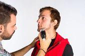 picture of barber razor  - Barber trimming a beard with an electric razor - JPG