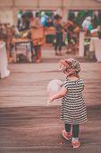picture of flea  - Little girl with her balloon walking inside an indoor flea market - JPG