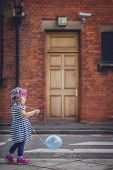 image of streetwalkers  - Little girl walking with her baloon on the London street