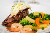 picture of lobster tail  - A seafood dinner of lobster tail shrimp and vegetables