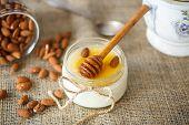 foto of yogurt  - homemade yogurt with honey and nuts in a glass jar - JPG