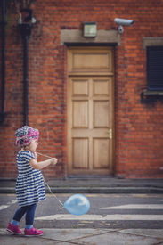 picture of streetwalkers  - Little girl walking with her baloon on the London street