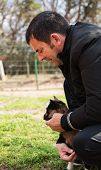 image of baby goat  - Farmer man gently holding brown baby goat - JPG