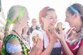 stock photo of national costume  - Friends visiting together Bavarian fair in national costume eating grilles sausage in bread roll - JPG