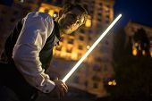stock photo of saber  - Handsome guy holding a lightsaber Jedi - JPG