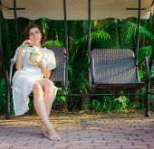 picture of swingset  - Woman drinks fresh coconut on the swinset - JPG