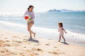 picture of hispanic  - Pretty young Hispanic mother having fun and playing ball with her daughter at the beach - JPG