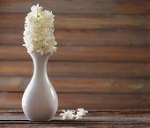 stock photo of vase flowers  - Beautiful white hyacinth flower in vase on table on wooden background - JPG