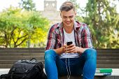 picture of staircases  - Happy male student listening to MP3 Player and smiling while sitting at the outdoors staircase with book and backpack laying near him - JPG