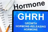 image of hormones  - Papers with hormones list and tablet  with words Growth hormone - JPG