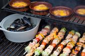 stock photo of grilled sausage  - Delicious seafood outdoor meal at the BBQ with grilled salmon shish kebabs marine mussels and individual pots of sausage stew close up view on the grill - JPG