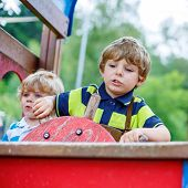 image of imaginary  - Two funny little kid boys pretends driving an imaginary car on children playground outdoors. On warm summer day. ** Note: Soft Focus at 100%, best at smaller sizes - JPG