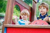 stock photo of imaginary  - Two funny little kid boys pretends driving an imaginary car on children playground outdoors - JPG