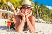 pic of sunbather  - young happy beautiful woman enjoying summer vacation on tropical sand beach - JPG