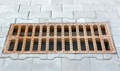 stock photo of grating  - Rusty cast iron storm sewer grating on the sidewalk stacked gray tiles - JPG