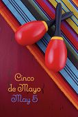 stock photo of mexican  - Happy Cinco de Mayo concept with maracas on Mexican style fabric on red wood distressed table - JPG