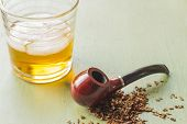 stock photo of tobacco-pipe  - Tobacco pipe on rustic warn green wood surface with spilled natural tobacco and a glass of whisky on the rocks - JPG