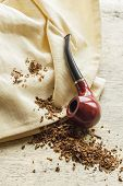 image of tobacco leaf  - Tobacco pipe on rustic warn wood surface with spilled natural tobacco - JPG