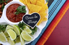 foto of mexican fiesta  - Happy Cinco de Mayo party table with food platter including limes corn chips chilli beans and salsa on a red wood background - JPG