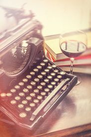picture of old vintage typewriter  - Old vintage typewriter with glass of wine pencils and books in this retro creative writing and relazation themed desk top - JPG