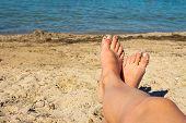 pic of sunbathing woman  - Female feet on the blue sea background - JPG