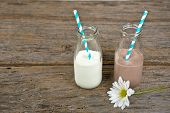 foto of white-milk  - White and chocolate milk in retro glass milk bottles with striped straw and white daisy on rustic wood - JPG