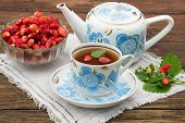 stock photo of teapot  - Fresh strawberry tea in an old bowl with a national ornament teapot ripe strawberries in a vase a bouquet of strawberries on linen napkins and old wooden table - JPG