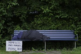 stock photo of scourge  - Homeless sleeping man on a park bench - JPG