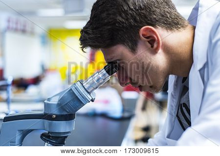 poster of a young medical or scientific researcher or doctor looking through a microscope, a male researcher working in a lab, side view of male medical worker in research laboratory