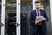 Technician using digital tablet in server room poster