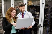 Technicians using laptop while analyzing server in server room poster