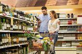sale, consumerism, alcohol and people concept - happy couple with bottle of white wine and food in s poster