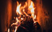 Burning Logs And Coal In Fireplace. Warm  Fire Burning In Dark Furnace. Burning  Pieces Of Wood In F poster