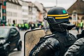 Rear View Of Police Officer Wearing Helmet And Shield Securing The Zone In Frong Of The Yellow Vests poster