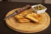Detail Of Hot Sandwiches On A Wooden Cutting Board Ready For Eating. Selective Focus On The Sandwich poster