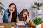 Mother Becoming Frustrated With Daughter Whilst Doing Homework Sitting At The Table At Home In Learn poster