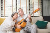 Meaningful Moments. Lover Senior Couple Sing A Song Together. Husband Playing A Guitar And Wife Is S poster