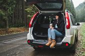 Young Pretty Woman Sitting In Suv Car Trunk At Road Side Drinking Hot Coffee At Road Side In Mountai poster
