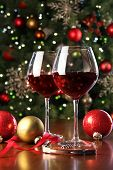 Glasses of red wine in front of Christmas tree for the holidays