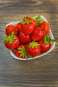 A Small White Porcelain Bowl Filled With Juicy Fresh Ripe Red Strawberries. Textured Table Top. Fres poster
