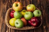 Wicker Basket With Ripe Multicolored Apples On Rustic Wooden Table poster