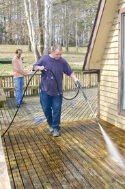 stock photo of pressure-wash  - Contractor pressure washing deck that raps around house getting home ready to sell - JPG