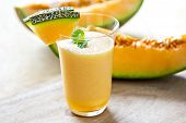stock photo of cantaloupe  - Cantaloupe smoothie in a glass by fresh cantaloupe - JPG