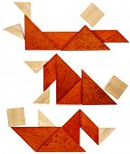 foto of tangram  - three abstract figures lying down and resting  built from seven tangram wooden pieces - JPG