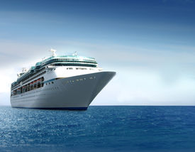 stock photo of cruise ship  - Cruise ship shot at angle at water level on a clear day with calm seas and blue sky - JPG
