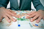 image of greedy  - man in suit sitting in a desk full of euro bills trying to hold them depicting wealth or greediness - JPG