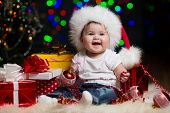 pic of santa baby  - baby girl in Santa Claus hat with gifts under Christmas tree - JPG