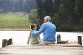 stock photo of older men  - Senior man fishing with grandson - JPG